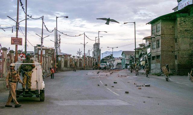 Indian security personnel walk on kashmir