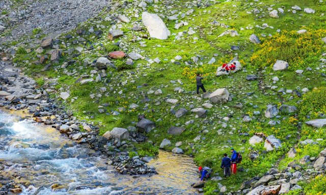 14 Trekkers and tourists rest in scenic Janshai meadows.