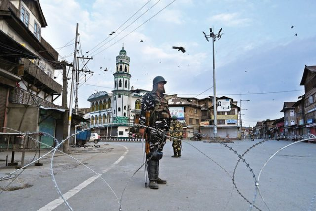 Security personnel stand guard on a street during a lockdown in Srinagar on August 12, 2019. Indian troops clamped tight restrictions on mosques across Kashmir for Eid al-Adha festival, fearing anti-government protests over the stripping of the Muslim-majority region's autonomy, according to residents.