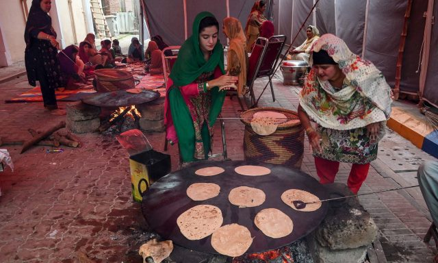 Sikh pilgrims prepare bread for devotees at a shrine in Nankana Sahib, some 75 kms west of Lahore on November 7, 2019, on the occasion of the 550th birth anniversary of Guru Nanak Dev. - A corridor that will allow Sikhs to cross from India into Pakistan to visit one of the religion's holiest sites is set to open on November 9, with thousands expected to make a pilgrimage interrupted by decades of conflict. (Photo by Arif ALI / AFP)