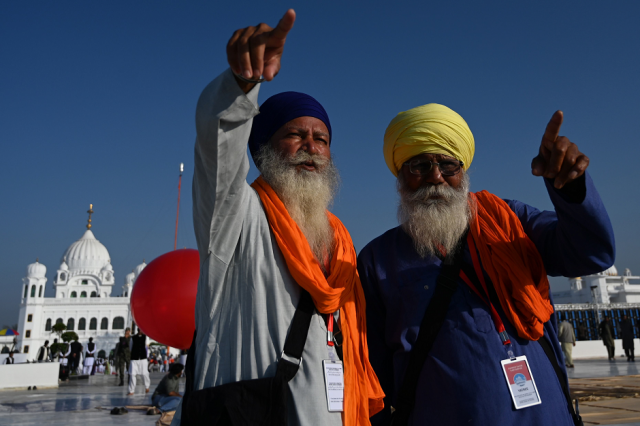 Sikh pilgrims point at the inauguration site of the Shrine of Baba Guru Nanak Dev at Gurdwara Darbar Sahib in Kartarpur