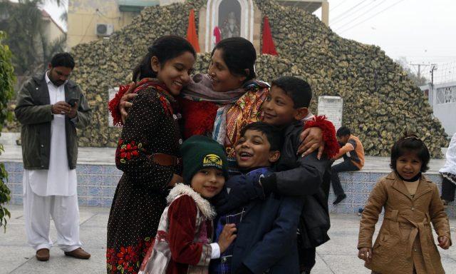 A Christian family greet each other after attending Christmas Mass at a church in Multan, Pakistan,