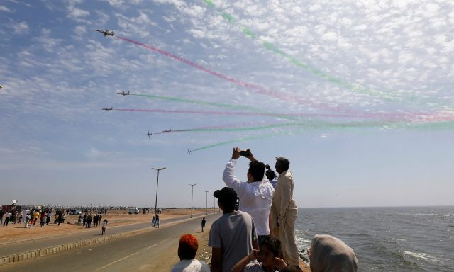 People take photos as Pakistan Air Force jets perform to commemorate Pakistan Air Force's 'Operation Swift Retort', during an air show in Karachi