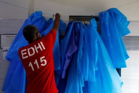 A volunteer of the Edhi Foundation, a non-profit social welfare programme, hangs up raincoats to be used to handle suspected carriers of the coronavirus disease (COVID-19), in Karachi, Pakistan March