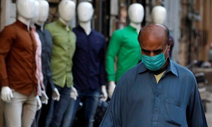 A man wears a face mask as a preventive measure, after Pakistan confirms fifth coronavirus case, walks in a market Karachi
