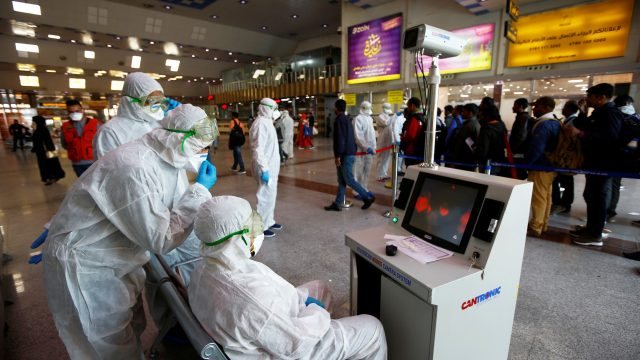 Medical staff in protective gear look at a screen while checking temperatures of passengers