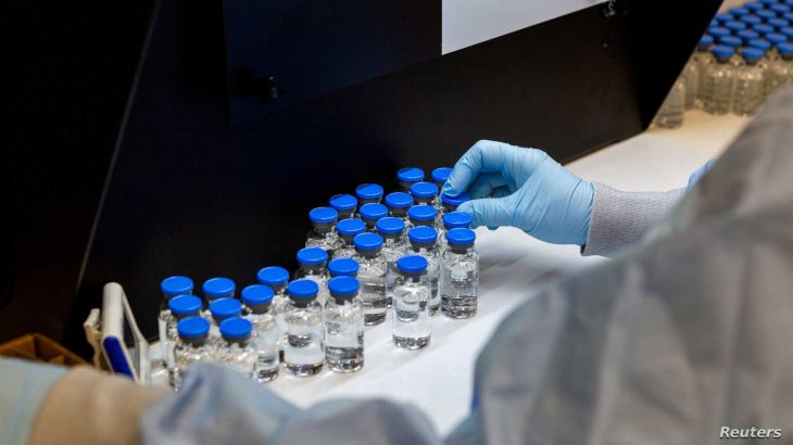 A lab technician inspects filled vials of investigational remdesivir at a Gilead Sciences facility in La Verne