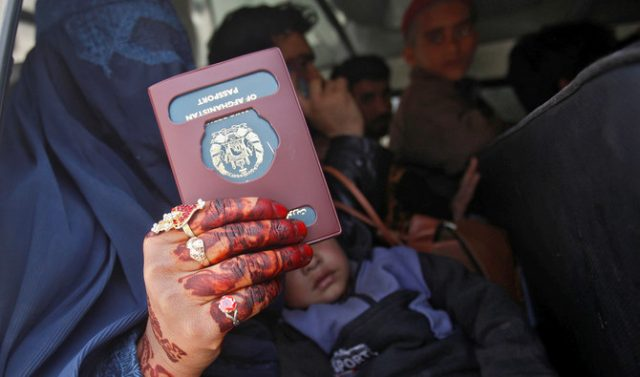 An Afghan woman holds her passport for the camera as she arrived with others to return to their home country at the border post in Torkham