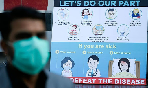 A man wearing a facemask walks past a sign board displaying preventive meausres against the spread of the COVID-19 novel coronavirus, outside a mall in Islamabad
